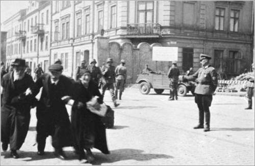Three elderly Jews walk arm-in-arm through the streets of Krakow during the final liquidation action of the ghetto.jpg